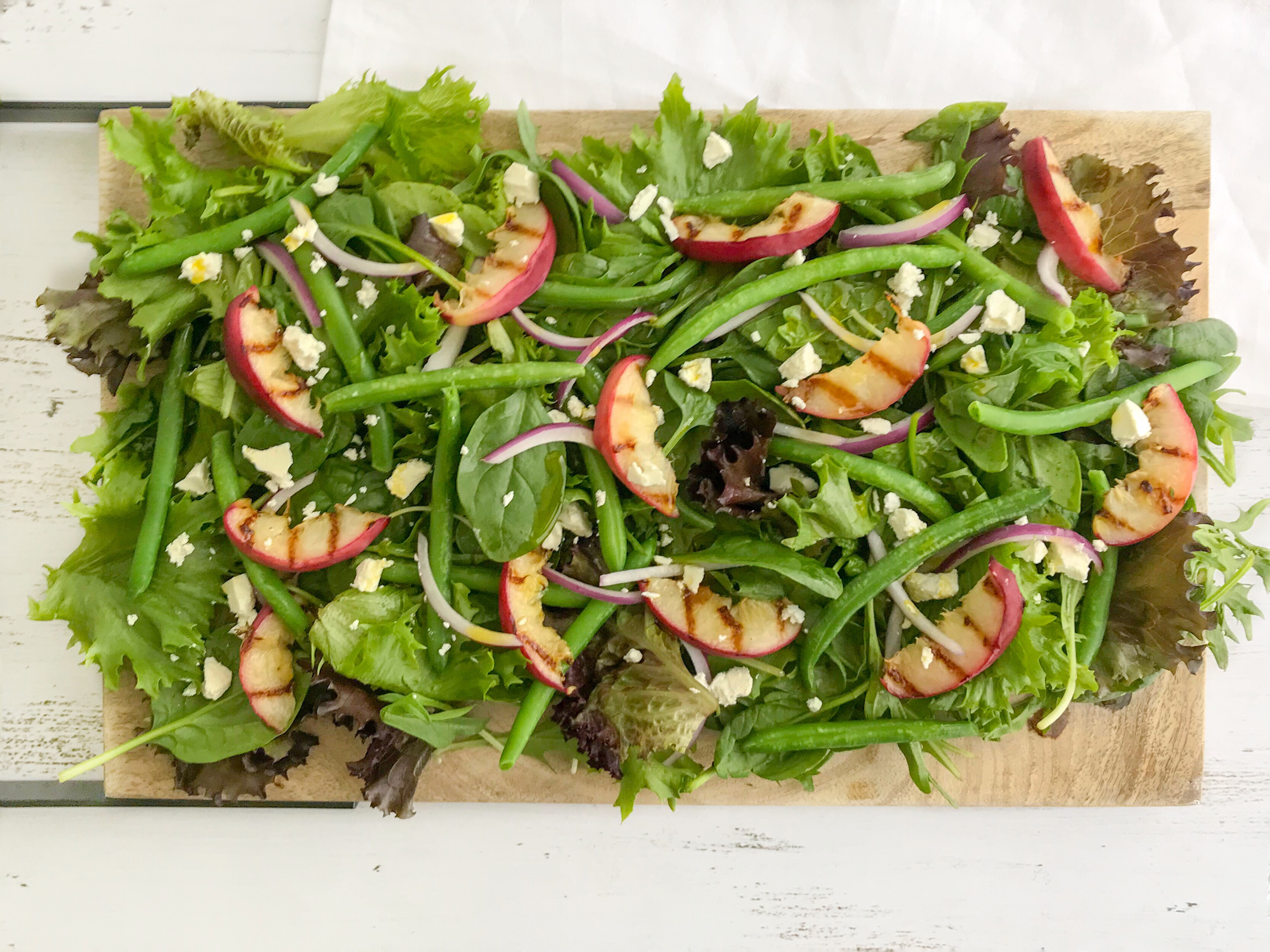 Grilled peach, green bean and almond salad spread out on a wooden platter