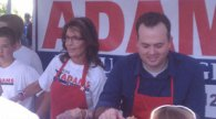 Closeup of Sarah and Kirk Adams serving at rally
