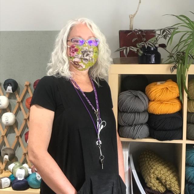 Sarah standing in Woven Art Yarn Shop, wearing mask