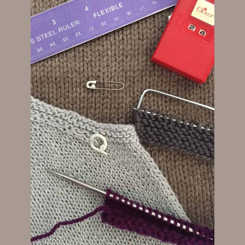 knitting tools - ruler, row counter, stitch markers laying on dark brown and light natural knitting fabric