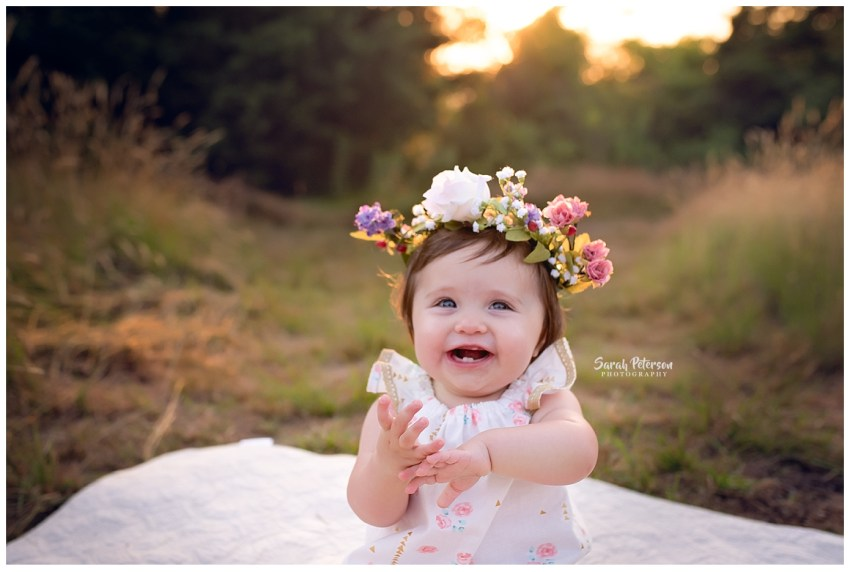 happy baby girl smiling with golden sunset in background