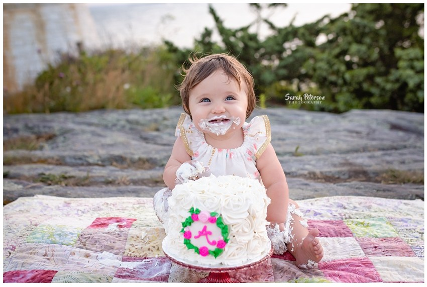 baby girl sitting with her birthday cake smiling