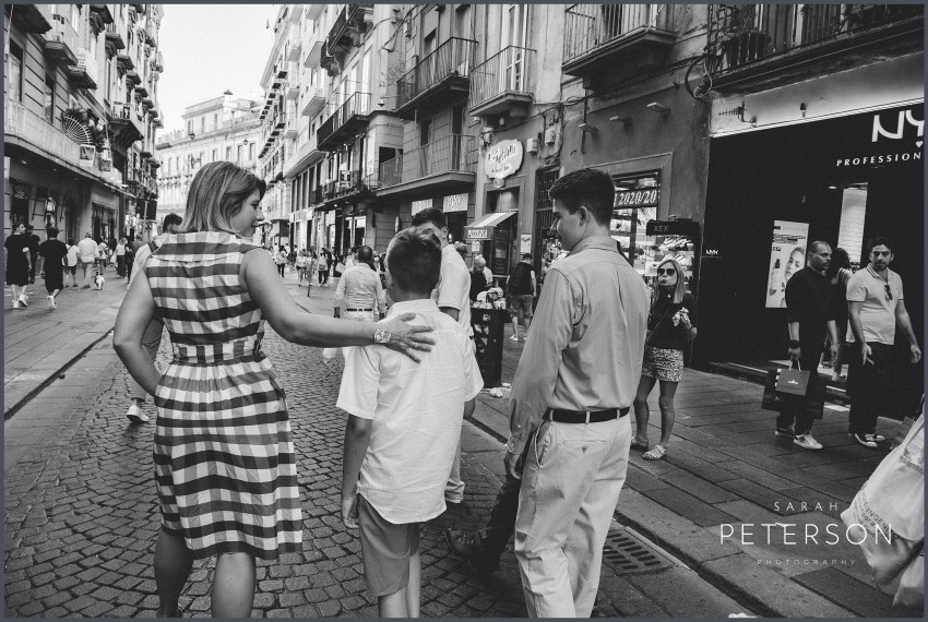 Family walking in busy street in downtown Naples Italy