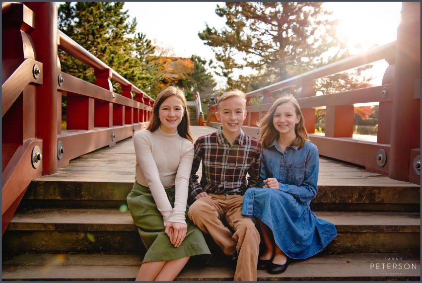 Three beautiful children sitting on a Japanese bridge near Yokosuka