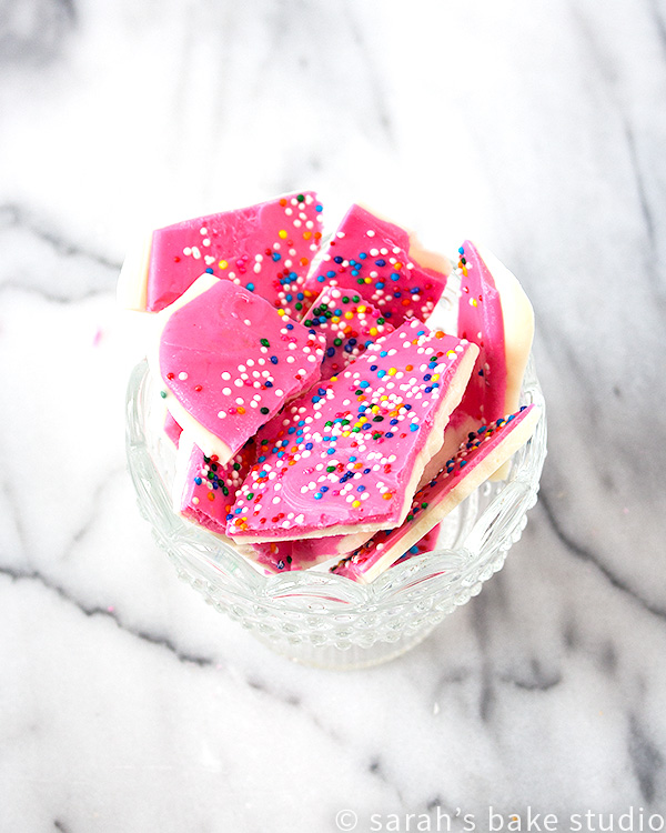 Frosted Circus Bark – melted white chocolate and pink chocolate wafers layered and decorated with colorful nonpareils; like Frosted Circus Animal Cookies but without the animals and cookies.