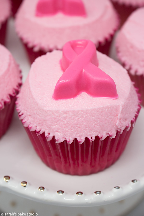 Pink Ribbon Pink Velvet Cupcakes – pink velvet cupcakes crowned with pink buttercream and adorned with white chocolate pink ribbons; a pinkalicous cupcake in honor of Breast Cancer Awareness Month.
