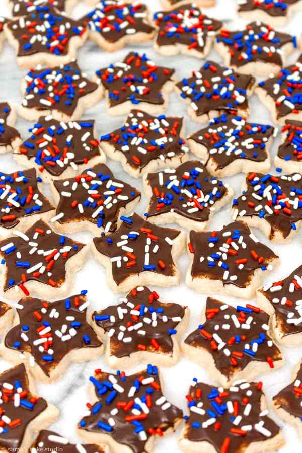Patriotic Star Sugar Cookies - star cutout sugar cookies frosted with melted chocolate and showered with red, white, and blue sprinkles for a patriotic twist to decorated cookies.