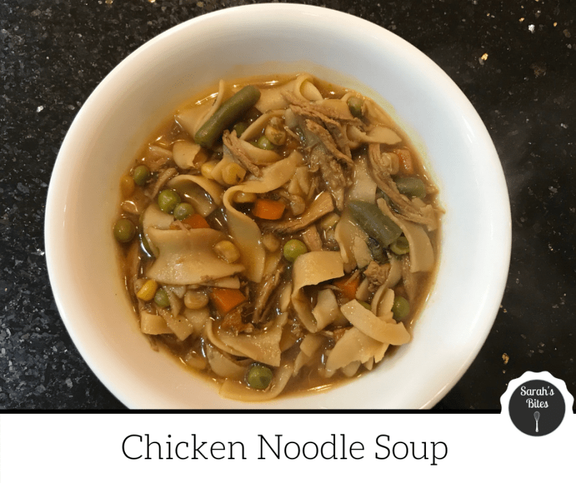 Chicken noodle soup with egg noodles, peas, carrots, and green beans in a bowl