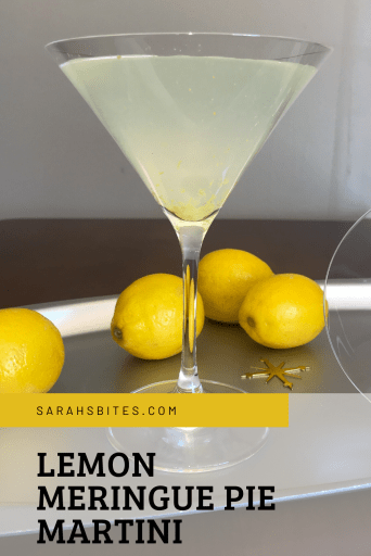 Martini glass filled with lemon meringue pie martini on a tray next to lemons and an empty martini glass on its side