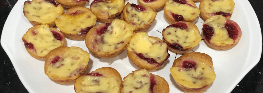 Round crescent rolls topped with gouda cheese and cranberry sauce, on a plate