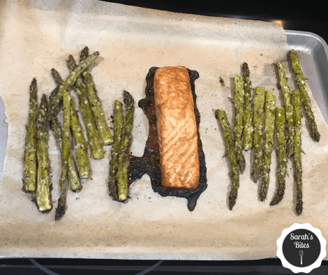 Asparagus on a sheet pan with salmon in the middle