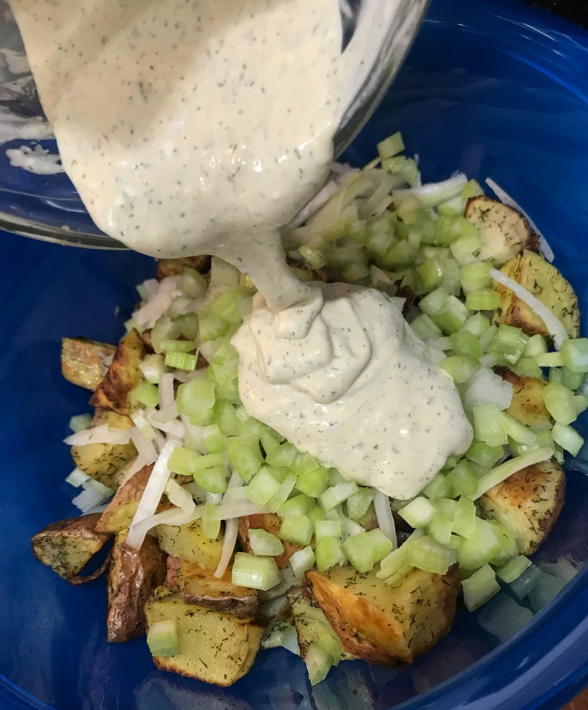 Salad dressing being poured onto a bowl of roasted potatoes with onion and celery