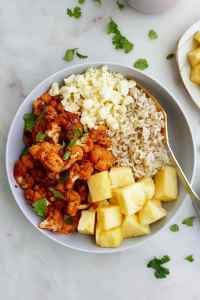 A bowl with pineapple, cauliflower, cheese, and rice