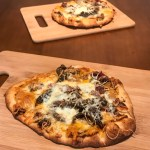 A small flatbread pizza topped with cheeses and pulled pork on a cutting board. In the background is a second flatbread on a cutting board.