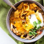 A bowl of chicken chili with cilantro, cheese, sour cream, and corn chips