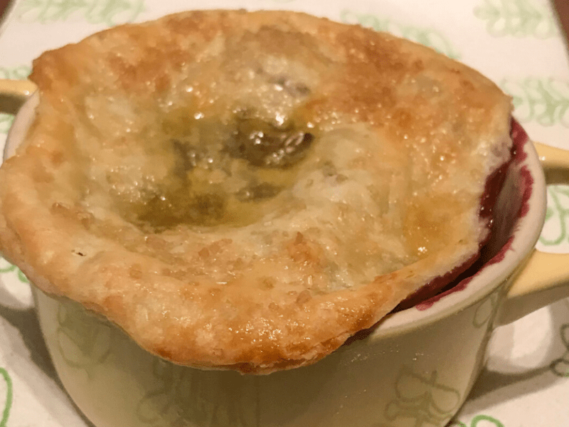 Mini cherry pie in a Le Creuset mini cocotte on a kitchen towel