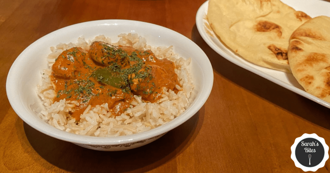 Cubed chicken in tikka masala sauce over basmati rice next to naan bread and a large pan. A logo says Sarah's Bites.