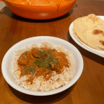 Cubed chicken in tikka masala sauce over basmati rice next to naan bread and a large pan