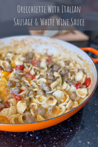 Pan of pasta with Italian sausage and tomatoes. Text over the image says Orecchiette With Italian Sausage & White Wine Sauce.