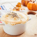 Pot pie in front of pumpkins.