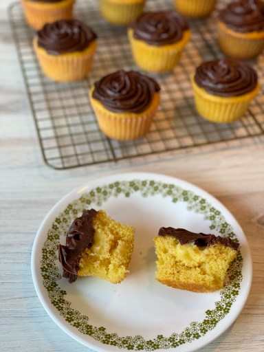 Plate with a cupcake cut in half. The cupcake is yellow and has a pudding filling and chocolate frosting. Behind the plate is a wire rack with whole yellow cupcakes with chocolate frosting.