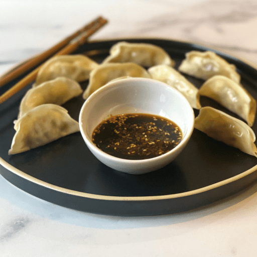 Small bowl of sauce in the middle of a plate of steamed dumplings with chopsticks on the side.