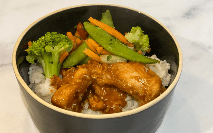 Bowl of white rice with chicken, broccoli, carrots, and snap peas.