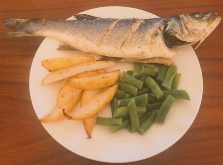 Sea bass, lemon wedges and beans