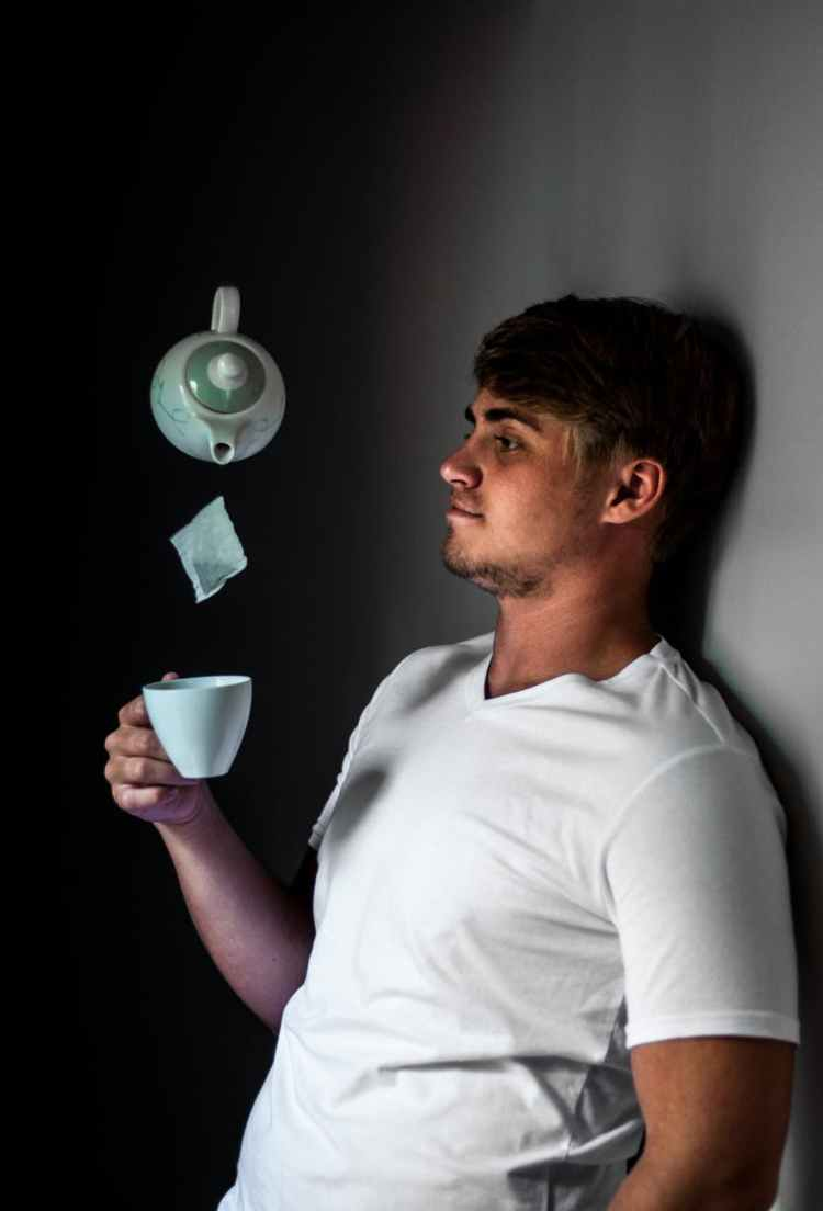 man leaning on wall while holding white ceramic cup