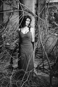 black and white photograph of a woman, artist Sarah Zar, in a room full of branches.