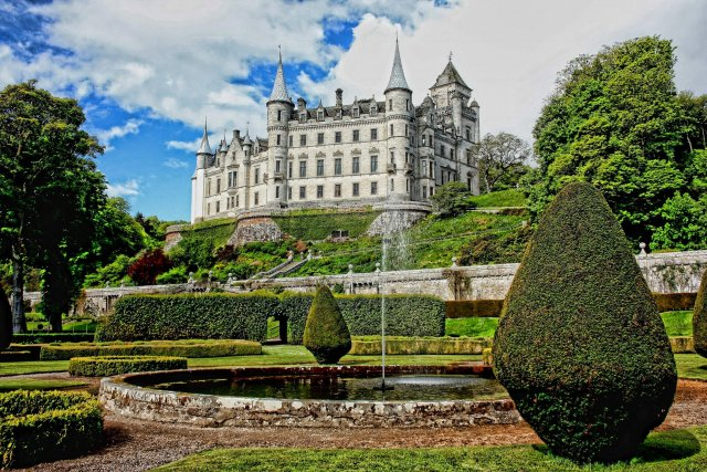 Picture of Dunrobin Castle, Scotland. A big castle in the background is complemented by beautiful landscaping and topiaries.