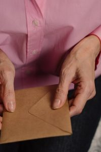 person in pink button up shirt holding brown paper