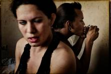 """San Pedro Sula, Honduras. May 2008. Deylin and Manuel """"la nelo"""" at their hotel room smoking crack. Deylin Monserrat is a transsexual commercial sex worker. She is HIV positive and lives in a small and destroyed hotel where she works and lives together with Manuel. Manuel Martinez """"la negra"""" is a transsexual commercial sex worker and he is HIV positive. They booth are addicted to crack, marihuana and alcohol."""