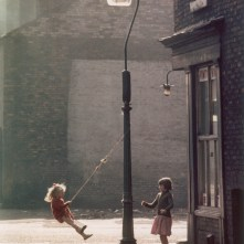 Two young girls swing on a rope attached to a pavement lampost outside a cornershop in Hulme, Manchester in the evening light. Photograph by Shirley Baker Date: 1965