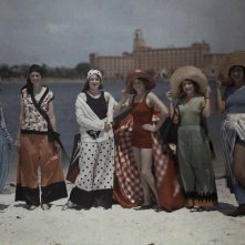 Women pose, in their beach attire, on a white sand beach in Florida.