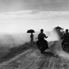 INDOCHINA (VIETNAM). May, 1954. Motorcyclists and woman walking on the road from Nam Dinh to Thai Binh.