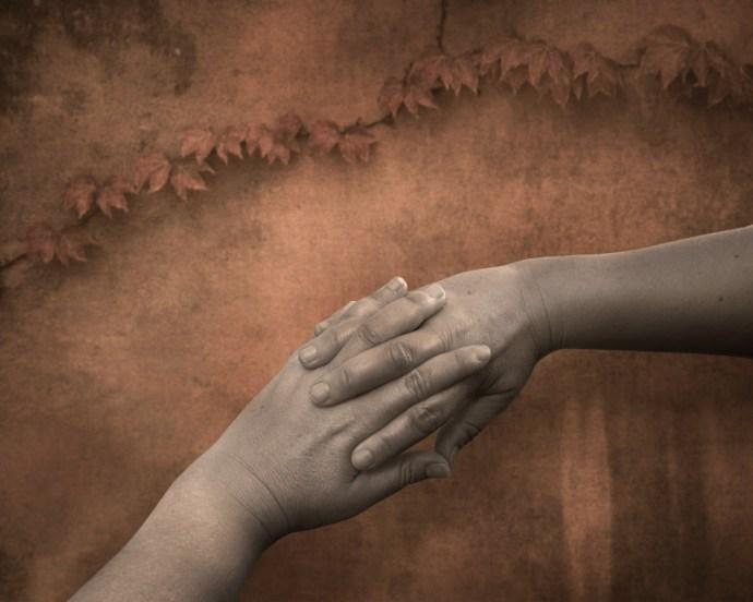 Interlocking fingers against a sepia rustic wall