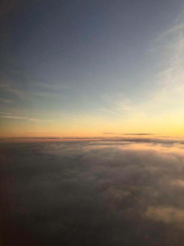 Utsikt från ett flygplansfönster. Ovanför molnen är himlen alltid blå.