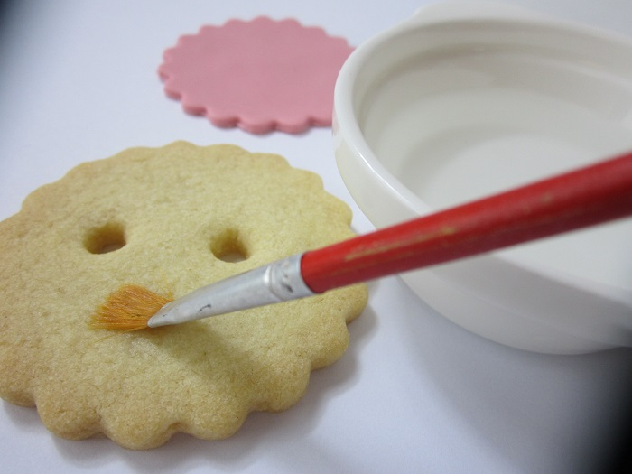 Brush the cookie with water to make it stick