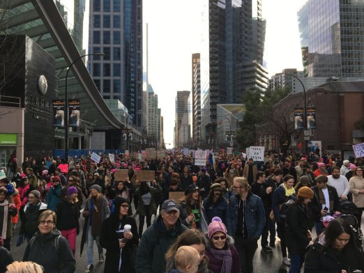 Large crowd of protestors with signs in front of Trump tower on a cold, gray day in Vancouver, BC