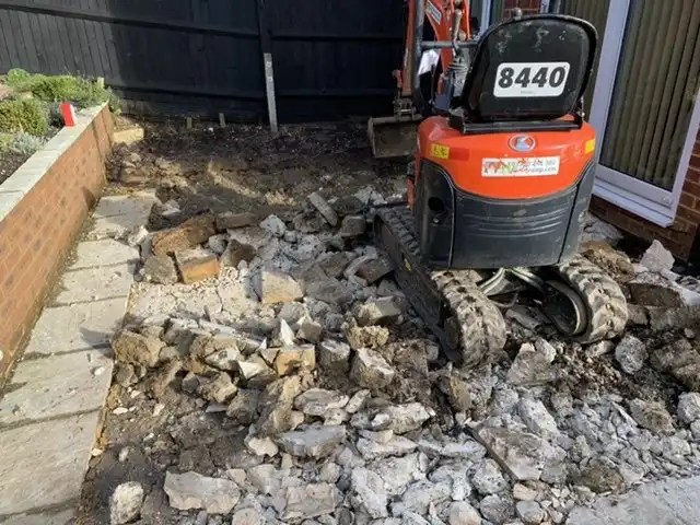 Breaking the concrete under the patio as part of our groundwork services