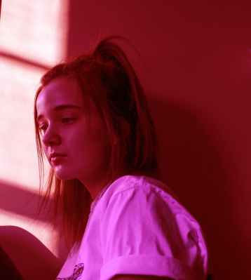girl beside brown wall