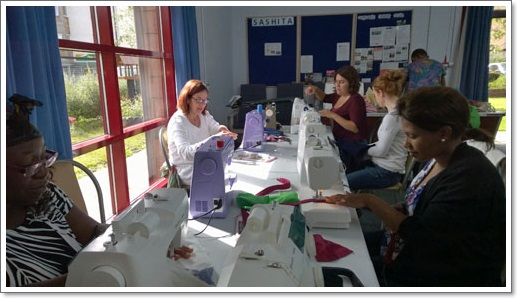 """Here are Alice, Elna, Silvia, Selena & Faith getting to grips with the sewing machines, whilst Modupe is standing in the background cutting out the fabric for her next creation!"""