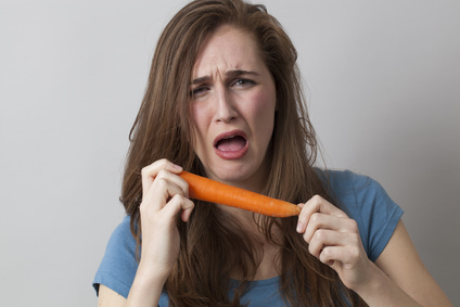 expressive young girl being disgusted in holding raw carrot for veggie disliking