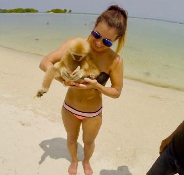 Girl holding monkey on beach