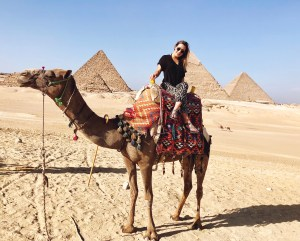 Girl on camel in front of great pyramids of Giza