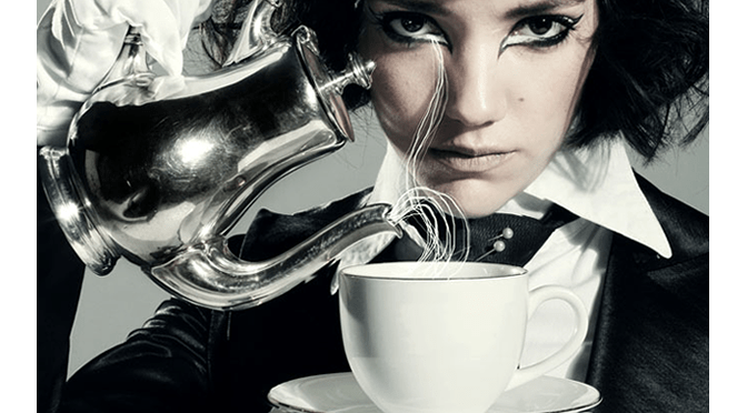 dark haired woman model pours teacup mad hatter