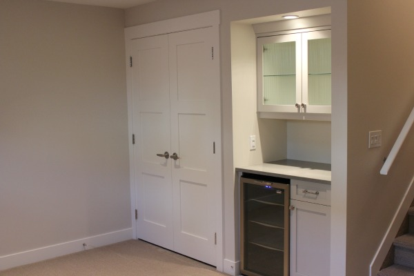 Basement Remodel - Basement Storage Room with Double Shaker Style Doors - Utilizing the Space Under the Stairs to Build a Snack Bar with Beverage Fridge