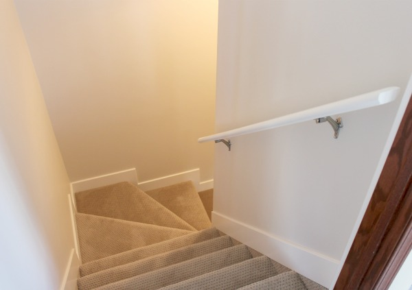 Basement Finishing Ideas - Basement Stairwell with Tan Carpet and White Shaker Style Trim