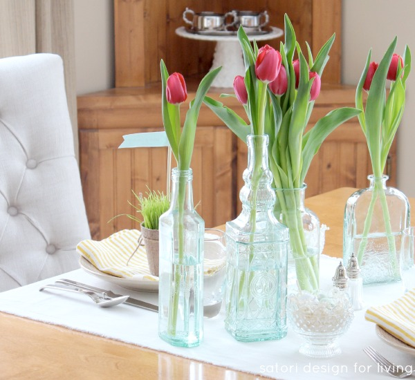 Easter Table Setting with Tulips in Green Glass Bottles and Vases